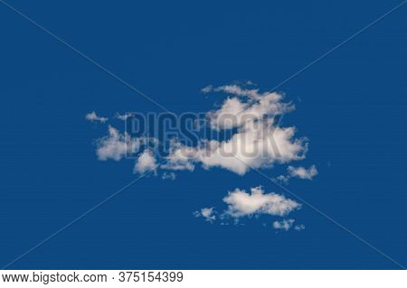 Light White Cumulus Clouds. A Small Group Of Clouds On A Blue Sky. Natural Sky Background.