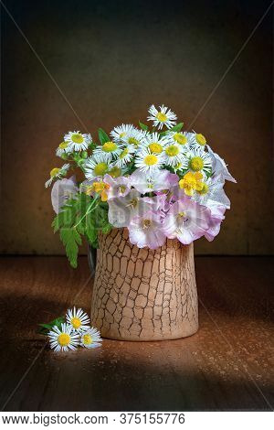 Still Life With Small Wildflowers On An Artistic Background. Bouquet Of Wildflowers In A Clay Vase.