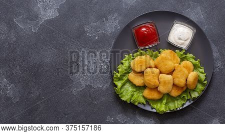 Tasty Crispy Fried Chicken Nuggets With Sauce On A Black Plate On A Stone Background.