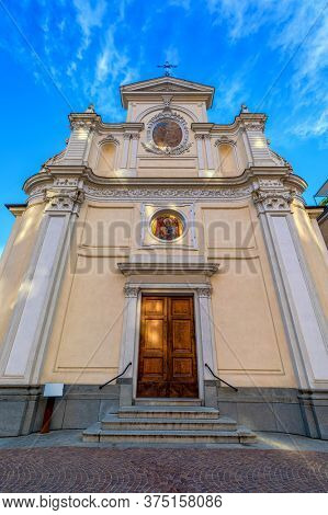 Facade of San Giovanni Battista catholic church under blue sky in old town of Alba in Piedmont, Northern Italy (low angle view, vertical composition).