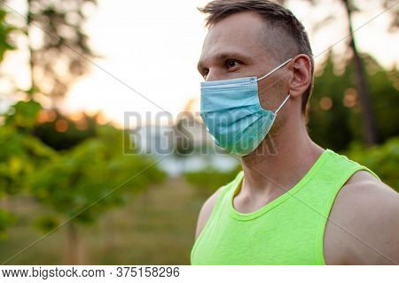 Muscular Jogger Wearing A Protective Mask During Covid-19 Quarantine At Sunset.