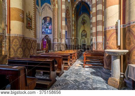 ALBA, ITALY - JUNE 14, 2020: Wooden pews, aisle and columns inside of San Lorenzo - a Roman Catholic cathedral aka Duomo dedicated to Saint Lawrence in small town of Alba in Piedmont, Northern Italy.