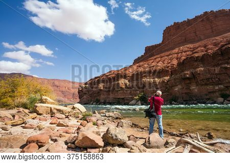 Man tourist with a photo bag photographs a beautiful landscape. USA. Lee's Ferry is a historic boat ferry across the Colorado River. The concept of active and photo tourism