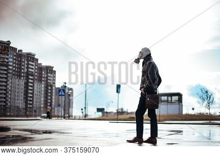 Casual Young Man In A Gas Mask Standing On The Street In An Infected City.