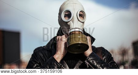 Close Up. Casual Guy In A Gas Mask On A City Background