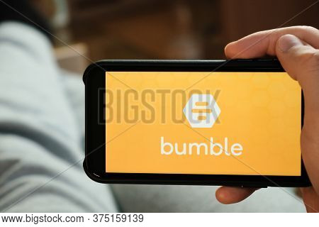 Bumble Application On The Smartphone In Mans Hand. Man Laying And Using Application For Dating And M