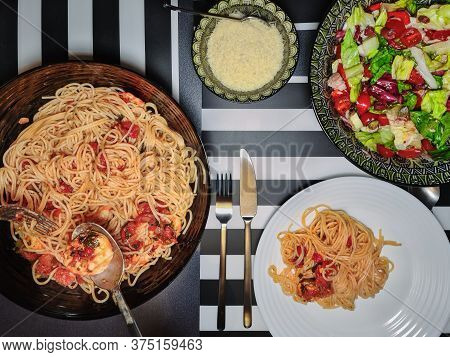 Home Italian Pasta With Shrimps Closeup Served On A Table With Colourful Salad & Parmesan. Top View
