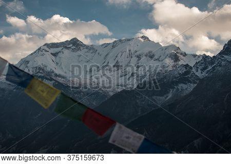 Buddhist Prayer Flags In The Snowy Nepalese Mountains, Annapurna Circuit, Himalaya