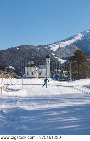 Cross-country Skier On Sunny Sport Track Towards Typical Austrian Pitoresque Church, Seefeld, Austri