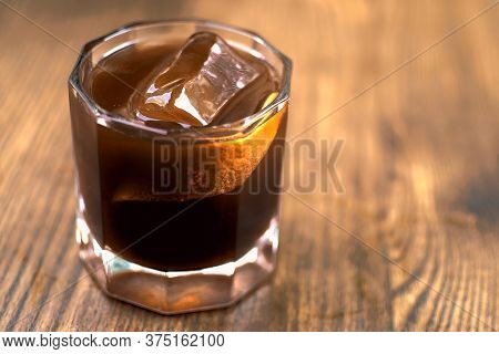 A Glass Of Coffee On Wooden Background. Iced Americano In Cafe. Cool Summer Drinks. Whiskey Coctail,