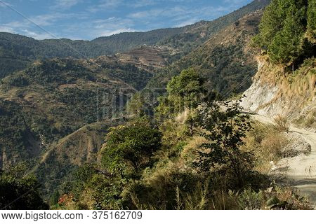 Dirt Road Going Uphill At Annapurna Circuit, Nepal With Rolling Hills In The Background