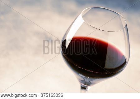 Red Wine From Grape Varieties Merlot In Glass, Gray Table, Selective Focus, Shallow Dof