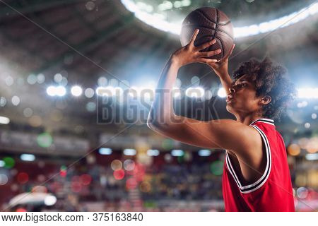 Basketball Player Throws The Ball In The Basket In The Stadium Full Of Spectators.