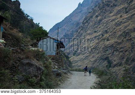 Father And Son On A Dirt Road By Beautiful Mountain Village, Annapurna Circuit