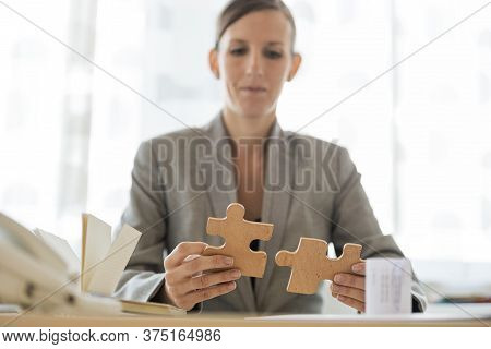 Businesswoman Sitting At Her Office Desk Joining Two Matching Puzzle Pieces In A Conceptual Image Of