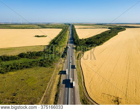 Left Hand Driving Motorway With Speedy Cars Surrounded By Green Rural Landscape Backgrounds.