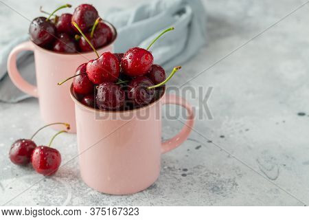 Two Pink Mugs With Fresh Ripe Cherries. Sweet Organic Berries On A Light Concrete Background. With C