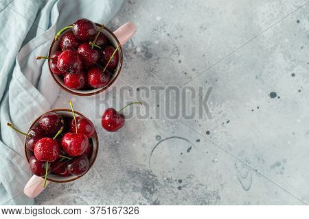 Two Pink Mugs With Fresh Ripe Cherries. Sweet Organic Berries On A Light Concrete Background. Top Vi