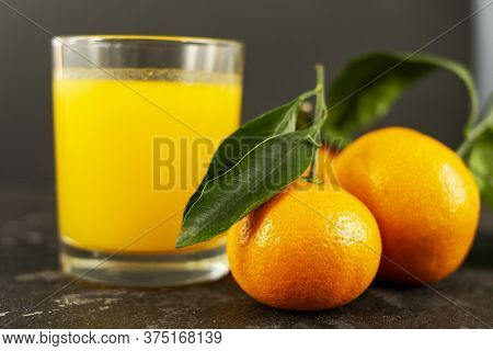Fresh Tangerine Juice In A Glass Cup On A Black Background. Whole Tangerines With Green Leaves Lie N