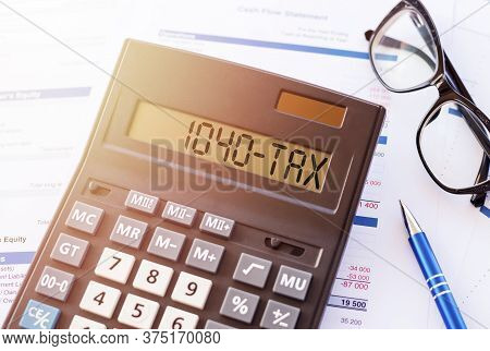 Word 1040-tax On Calculator. Business And Tax Concept.