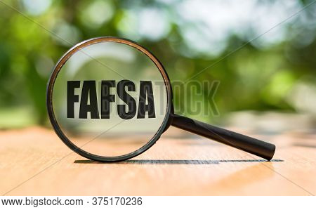 Free Application For Federal Student Aid - Fafsa Written On Magnifying Glass On Wooden Table And Gre