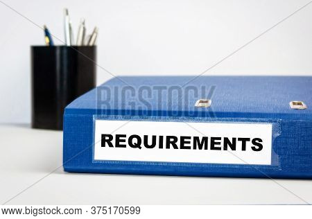 Requirements - Blue Binding On A Table In An Office With A Pencil Box.