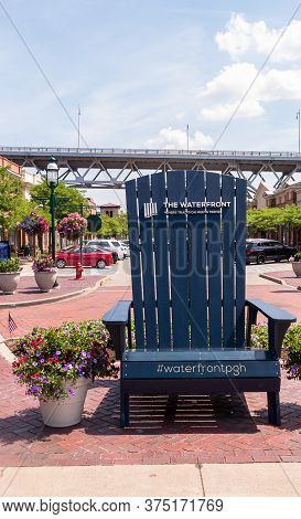 Homestead, Pennsylvania, Usa 7/5/20 An Oversized Adirondack Chair In A Sitting Area In The Waterfron