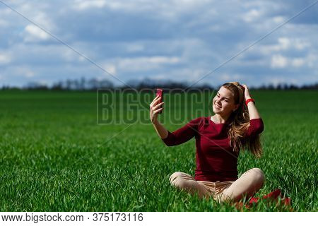 Young Beautiful Woman Student With A Phone In Her Hands Sitting On The Grass. Girl Takes Selfies And