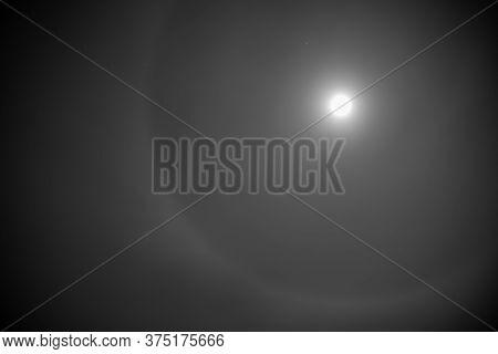 Halo Phenomenon Around The Full Moon In The Dark Sky