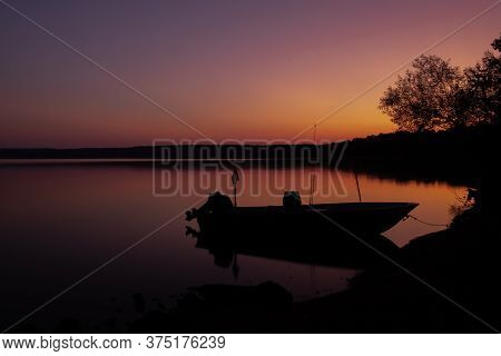 Beautiful Early Morning Twilight Scene Of The Silhouette Of A Fishing Boat Tied Along The Shoreline