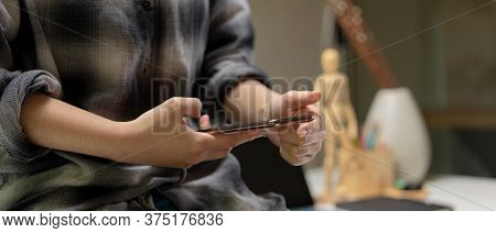 Female Worker Sitting On Worktable And Using Smartphone To Contact Customer In Office Room