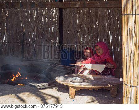Bedouin Village In Desert, Egypt - February 2020: Two Arabian Girls Preparing Food Near Fireplace, M