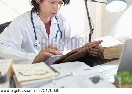 Asian Doctor Researching Reading Medical Books And Online Knowledge To Find Treatment Patient Guidel