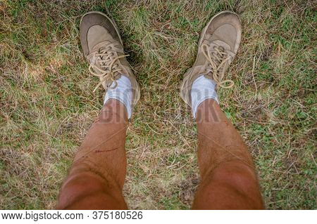 Legs Of Male Tourist Hiking In Mountains And Wearing Unsafe Outfit