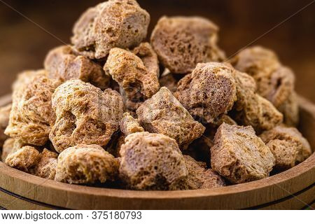 Vegan Food, Coarse Soy Protein, Also Called Soy Meat, The Protein Textured In Pieces Inside A Wooden