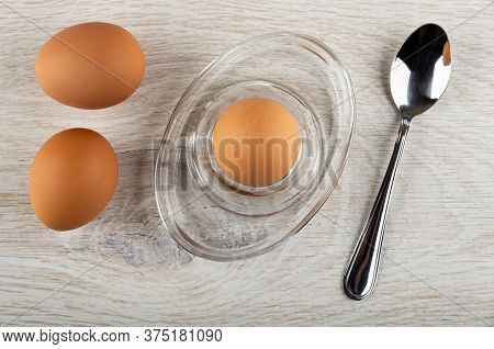 Brown Unpeeled Boiled Eggs, Egg On Glass Egg Stand, Teaspoon On Wooden Table. Top View