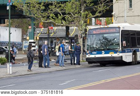 Bronx, New York/usa - May 18, 2020: People Board Public Bus While Wearing Masks During Covid-19 Pand