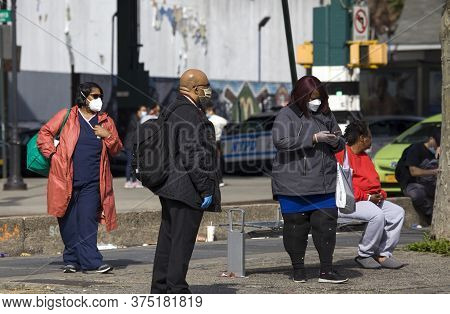 Bronx, New York/usa - May 20, 2020: People Wait For Public Bus While Wearing Mask During Covid-19 Pa