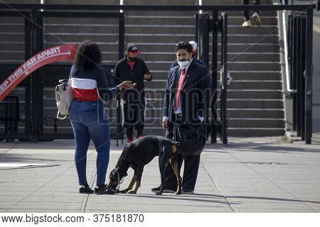 Bronx, New York/usa - May 20, 2020: Man Wearing Mask Talks To Woman During Covid-19 Pandemic.