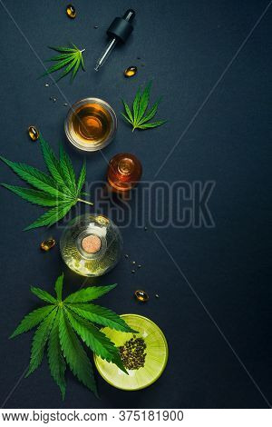 Medical Cbd Oil On Black Trendy Background With Cannabis Leaves. The Concept Of Medical Tincture Of