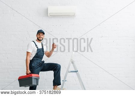 Workman In Uniform Holding Screwdriver Near Ladder And Air Conditioner On Wall