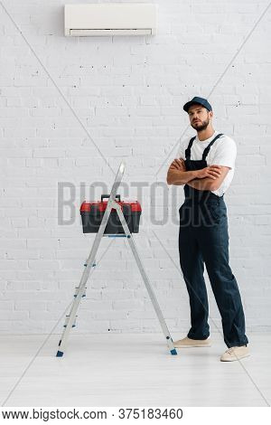 Workman In Overalls Looking At Camera Near Toolbox On Ladder And Air Conditioner On White Wall