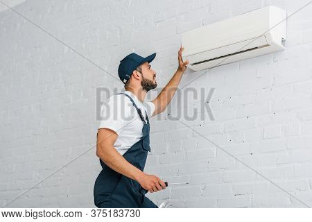 View Of Workman In Workwear Holding Screwdriver Near Air Conditioner