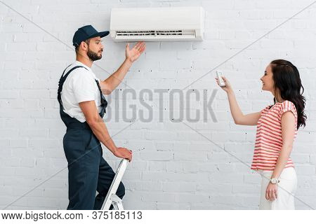 Side View Of Workman Pointing At Air Conditioner Near Smiling Woman Holding Remote