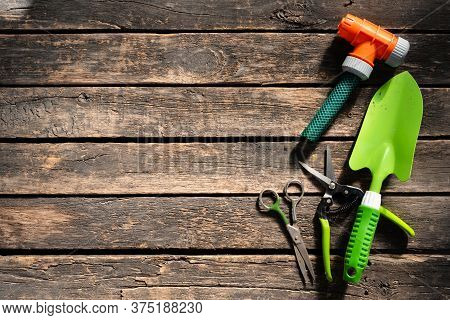Garden Tools On A Wooden Flat Lay Table Background With Copy Space. Shovel, Scissors, Garden Pruner