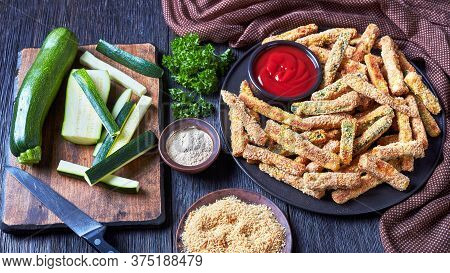 Crunchy Zucchini Sticks Breaded With Panko Breadcrumbs, Parmesan Cheese, Spices On A Black Plate Wit