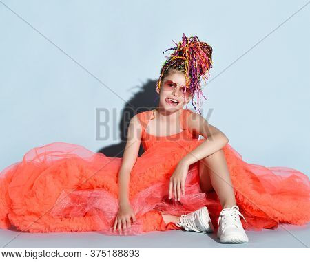 Frolic Girl With Colorful Dreadlocks In Coral Dress, Sneakers And Sunglasses Sits On Floor And Laugh