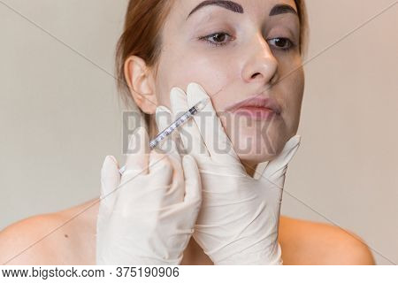 Natural Look Of Young Woman Gets Cosmetic Injection. Doctors Hands Making An Injection In Face. Beau