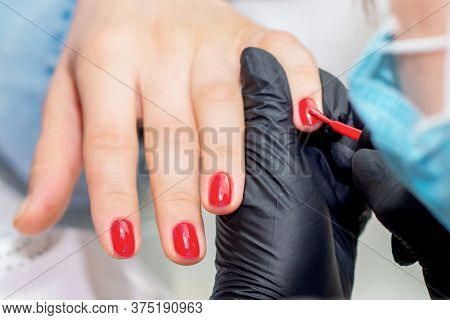 Close Up Manicurist Paints Fingernails With Red Nail Polish In Salon.