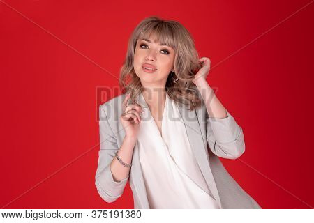Portrait Of A Woman Business Blonde In Bright Jacket On Redbackground .copy Space